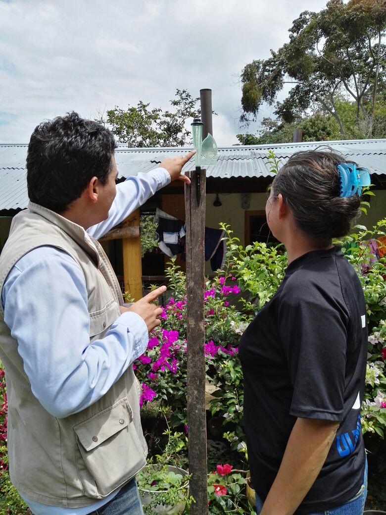 Mitchel Hernandez Agronomo explica pluviometro a campesina